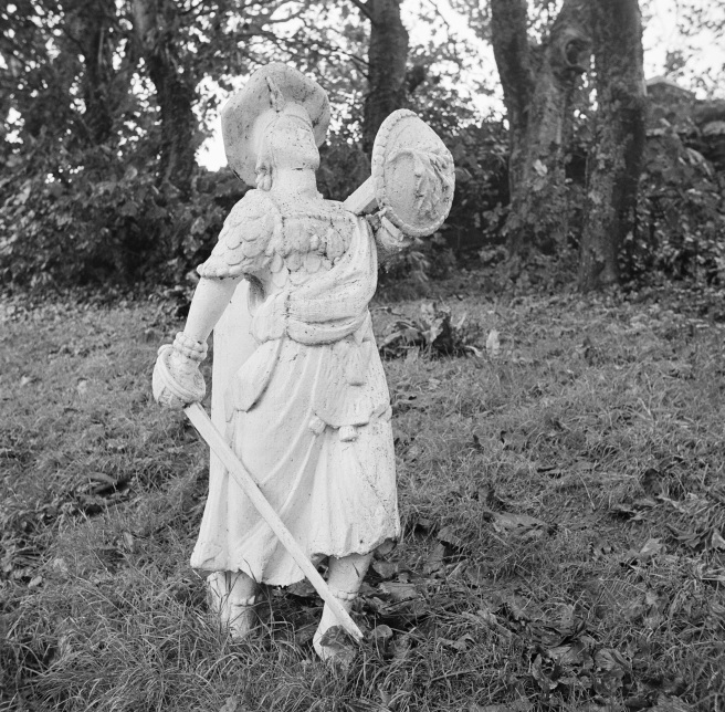 B&W photo of white-painted figurehead in Scottish dress with tam o'shanter, kilt, sword and shield, in churchyard.