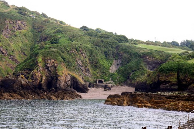 Photograph of rocky cove with steep, hilly sides covered in green. The tide is nearly at the entrance to the cove, which is very narrow.