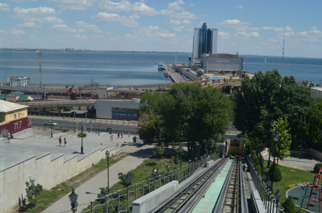 View of port city, with tree-lined plaza in foreground, looking out to sea over port infrastructure, and a blue sky beyond.