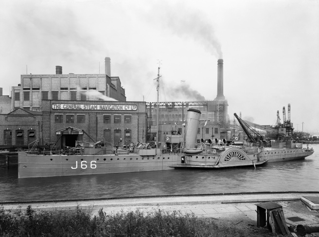 Black and white photograph of paddle steamer marked with pennant number J66 to the left, with its funnel echoed in the chimneys of the industrial buildings beyond.