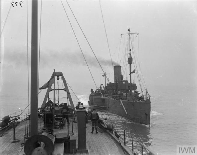 Black and white photograph taken from a steamer at sea showing another paddle steamer beyond and on the right.