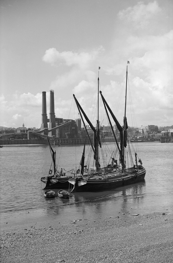B&W photograph of Thames with the masts with furled sails of two barges at their moorings in the foreground being echoed by the two tall towers of the power station to the left centre ground, on the opposite bank of the river, under a clear sky with puffy white clouds.