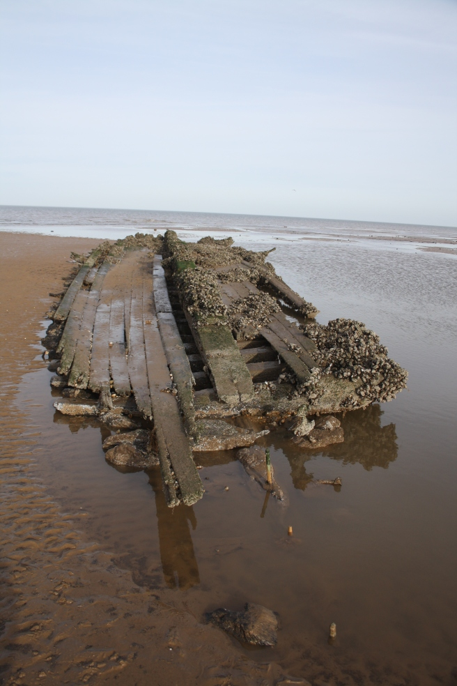Collapsed hull of wreck still retaining its 'boat shape', half in water to the right, on an extensive beach under a blue sky.
