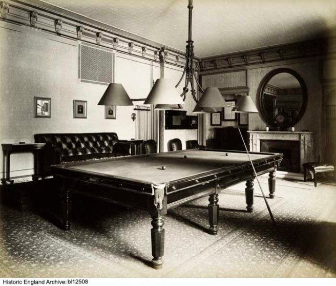 Black and white photograph of a billiard table in a room decorated in late Victorian style, with three lampshades low over the table.