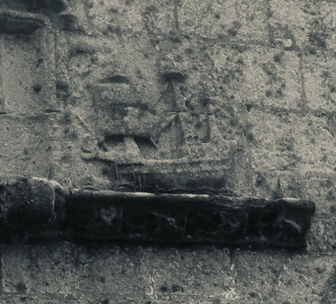 Modern black & white photo of a stone ledge on a wall with a carved relief of a sailing ship.