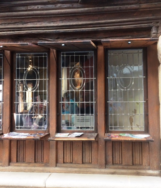 Modern colour photo of 3 glass windows set in a timber building, with horizontal shutters open above and below the windows, the lower shutters acting as counters (used to display literature on the building, formerly as a shop).