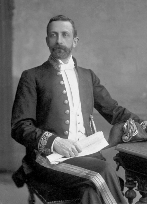 Historic B&W photo of seated man in dark moustache and beard, wearing a formal dress uniform with gold braid to his cuffs and trousers, holding a scroll in his right hand and a gold braided bicorn hat in his left.