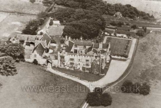 Historic B&W aerial photo of building complex with main courtyard house in centre, set in an open landscape with clumps of trees.