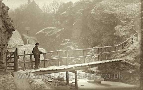 Historic sepia photo of man crossing a small footbridge over a river in light snow and ice conditions. ne gorge lightly dusted with snow.