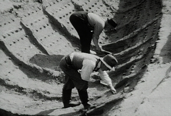 Historic 1939 B&W film still showing archaeologists at work within the 'ship-shape' with the ship structure visible in the sand, and all the rivets still in situ.