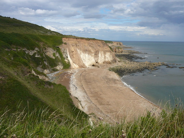 Colour photograph taken from the top of grass-covered cliffs on the left, looking down to an empty beach with bare, vertical cliffs rising from it at centre; to the right rocks and sea, all seen under a cloudy sky.