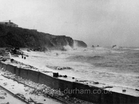 B&W photo of coastline with large waves crashing on cliffs to the left of the image.