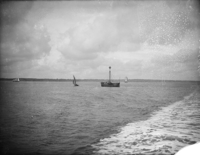 Historic black and white photograph looking towards a lightship at sea, identified by its mast and the name 'CALS. . . ' visible in large white letters to the right of the hull, and a small yacht to the left. A tidal wash is visible to right of the image, which is compromised by a broken right-hand corner and other damage across the upper sky visible in the original glass plate negative.