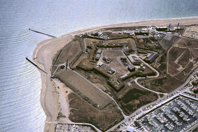 Modern aerial view of military complex facing the sea.
