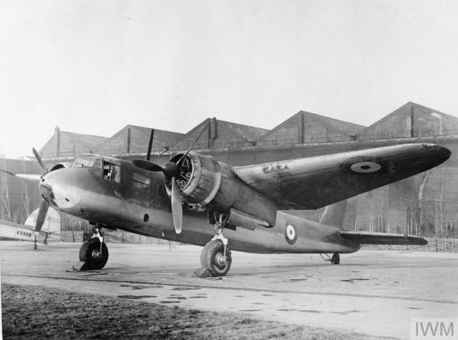 Historic B&W photograph of Blackburn Botha aircraft parked facing with its nose prop to the left in front of the gables of a hangar.