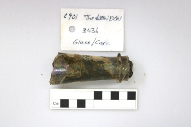 Archaeological record photo of glass bottle neck with scale and tag.