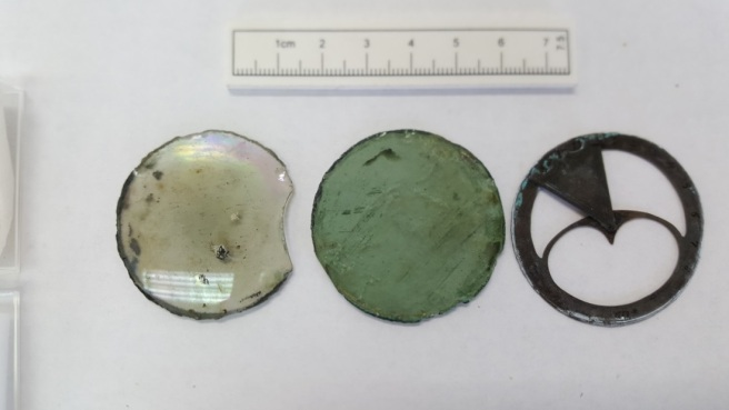 Two circular glass discs and a cut-out metal disc with a scale rule at top.