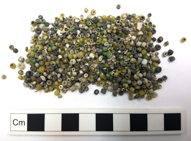 Beads in various shades of green with a scale rule underneath.