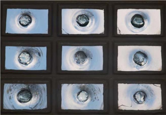 Nine bull's eye panes individually set in a dark multi-pane frame.