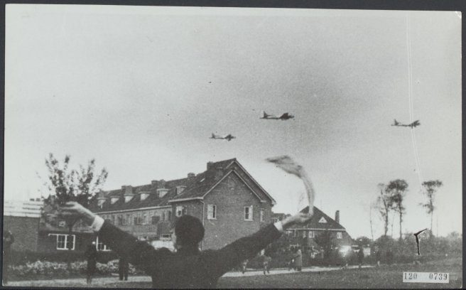 Black & white photo of Dutch citizen waving at three aircraft flying low over a town.