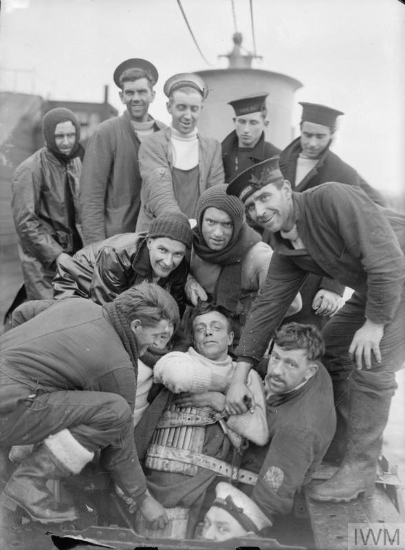 Historic B & W photograph of men surrounding a survivor in a cork lifejacket.