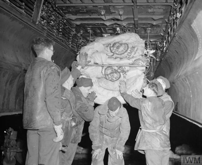 Historic B&W photo of six men loading the sacks, their uniforms streaked with escaped flour.