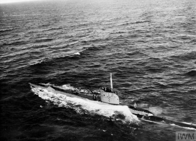Historic B&W photograph of submarine on the surface of an otherwise empty sea.